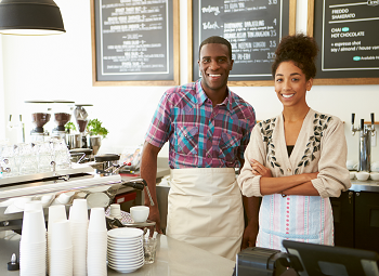 Man and woman small business owners posing in their coffee shop behind the counter